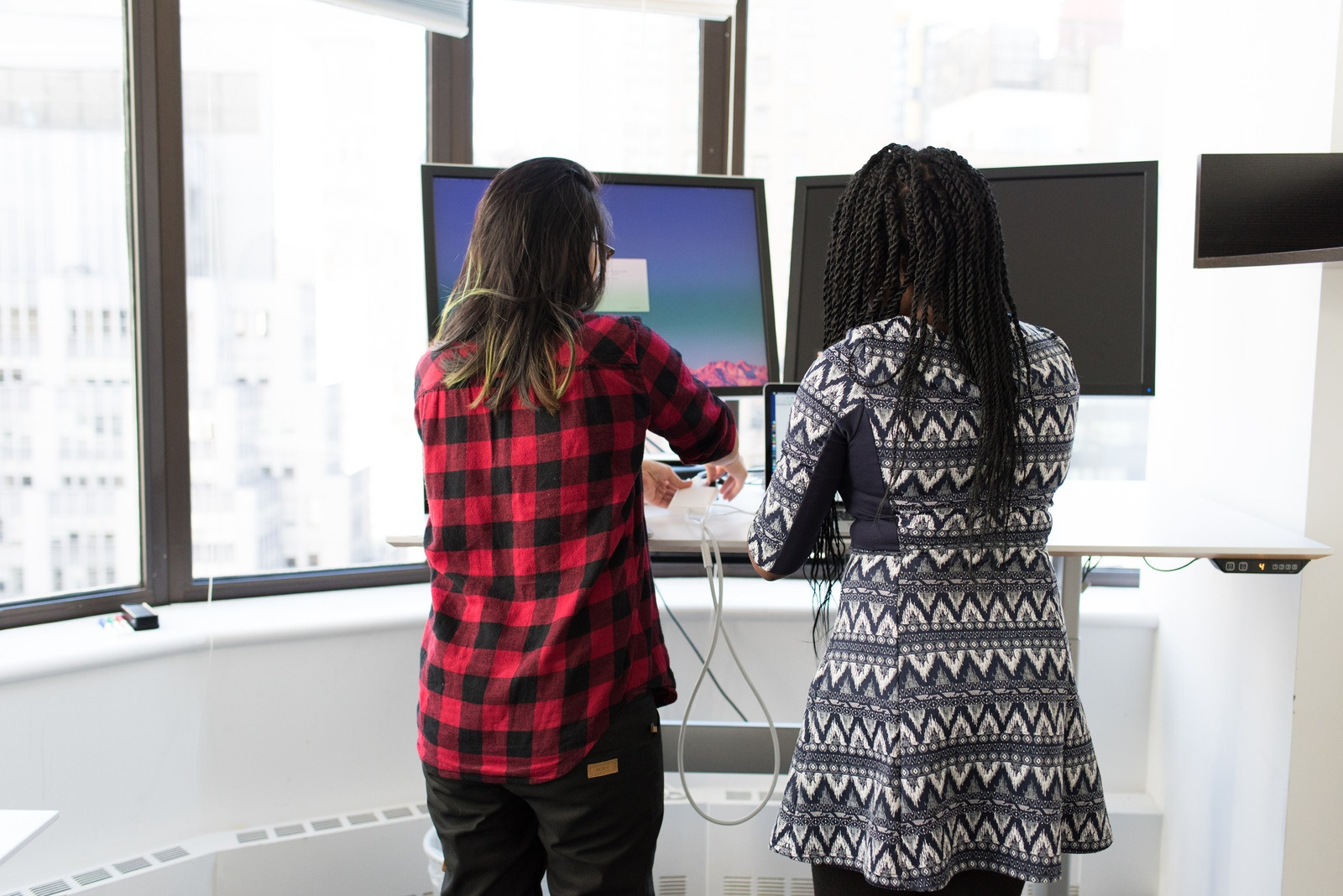 canva-two-women-standing-in-front-of-television-MADGv0r1P5I